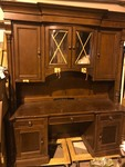 Large ornate wooden wall desk almost 8 feet tall comes into pieces bottom and top never been installed still has tape on curved glass doors in front high dollar desk